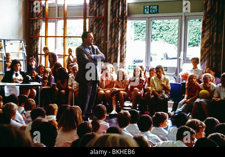 Primary School Head Teacher Talking To Students In Assembly - Stock Photo