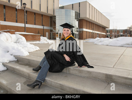 attractive blond woman in graduation uniform sitting in front of college building and smiling - Stock Photo