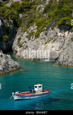 Small rocky bay with crystal clear waters and touristic boat in Zakynthos, Greece - Stock Photo