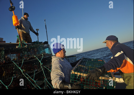Crew of a lobster boat in the Gulf of St. Lawrence setting traps on opening day of the spring season in New Brunswick, - Stock Photo