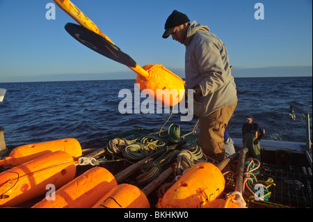 Crew member lobster boat in the Gulf of St. Lawrence getting ready to set a spar buoy to mark lobster traps New - Stock Photo