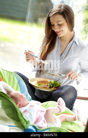 Mother eating whilst looking at baby - Stock Photo