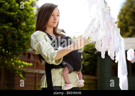 Woman with baby taking in washing from line - Stock Photo