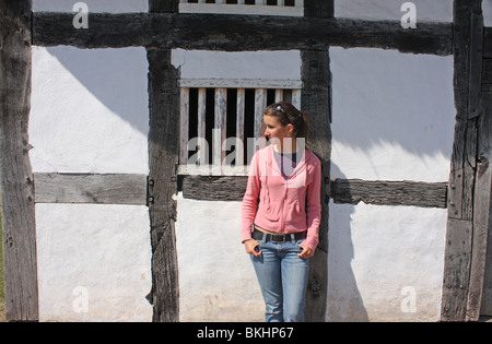 Young Welsh woman by Abernodwydd Farmhouse, a restored building at St Fagans National History Museum near Cardiff - Stock Photo