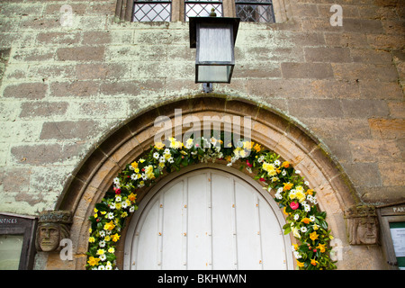 Porch lighy and flowers surronding the entrance to Tillington Church with it's Scots Crown Spire - Stock Photo