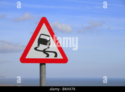 A road sign warns motorists of the potentially slippery surface near Eastbourne, East Sussex - Stock Photo
