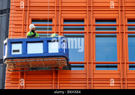 Man in cradle inspecting cladding on new high rise building - Stock Photo