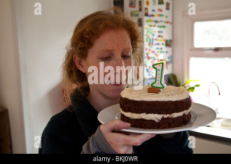 Redheaded woman looking at a chocolate, birthday cake with a number 1 candle. - Stock Photo