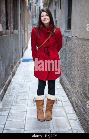 A tourist posing in one of the small alleys in Venice, Italy - Stock Photo