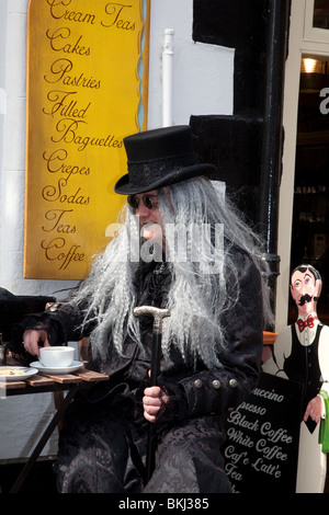 Taking Tea, A Man in fancy dress seated outside Whitby Tea Shop or cafe, at the Goth Festival, April, 2010 - Stock Photo