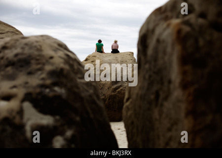 Two people sit on a rock at Tunnel Beach near Dunedin in New Zealand - Stock Photo