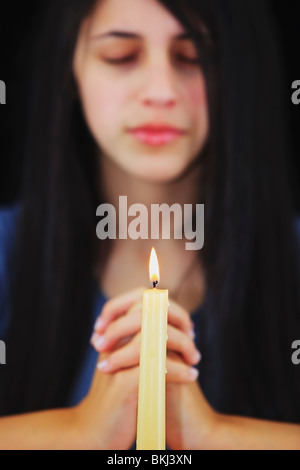 A Teenage Girl Praying With A Candle Lit - Stock Photo
