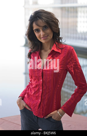 A beautiful young (Eastern) Indian woman stands and strikes an alluring pose. - Stock Photo