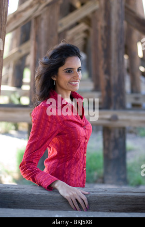 A beautiful young (Eastern) Indian woman stands leaning on a wood beam, looking off camera and smiling. - Stock Photo