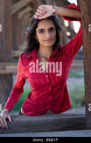 A beautiful young (Eastern) Indian woman is standing, leaning on a wood beam looking at peace with the world. - Stock Photo