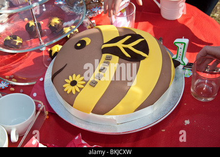 A birthday cake in the shape of a bee. - Stock Photo