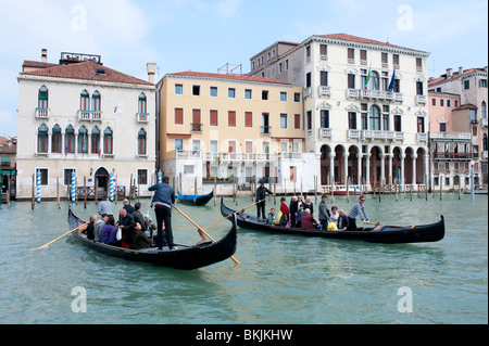 Two traditional traghetto public ferry gondolas ferrying people across Grand Canal in Venice Italy - Stock Photo