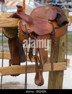 western saddle sits atop wooden fence during Pioneer Days High Springs Florida - Stock Photo