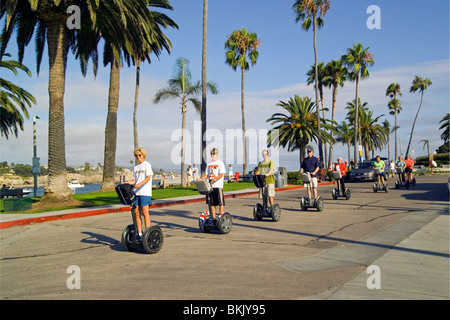 Visitors enjoy a unique way to tour around Newport Beach, California, USA, by riding a Segway, the world's first - Stock Photo