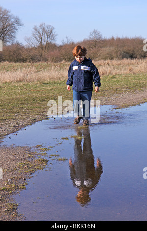 portrait of a young boy walking through a puddle - Stock Photo