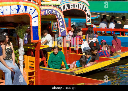 Colorful trajineras travel on the Xochimilco canals within Mexico City, Mexico. - Stock Photo