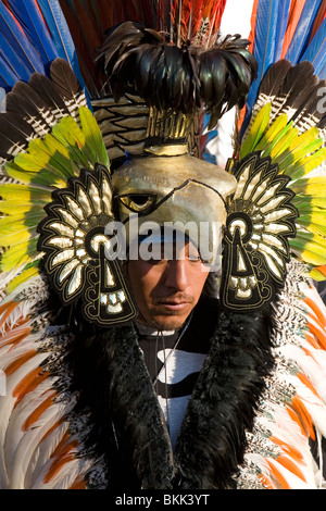 Native Aztec people dance wearing tradional costume in the Zocalo of Mexico City, Mexico. - Stock Photo