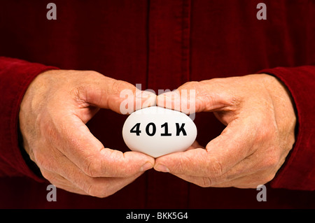 Man holds egg with 401k written on it - a retirement savings plan in the United States of America - Stock Photo