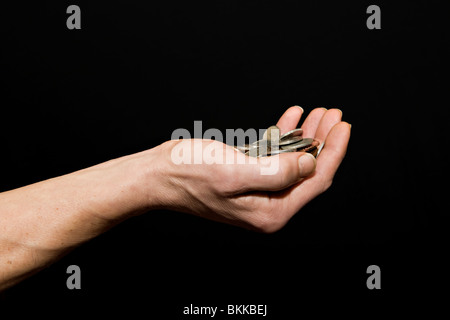 Caucasian male (42 yrs old) with hand held out full of money against a black background - Stock Photo
