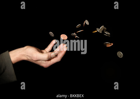 Caucasian male (42 yrs old) hand with money in the air depicting the concept of 'throwing money away' - Stock Photo