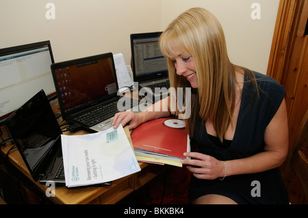 Working from home a woman working on annual accounts from a small office within her house - Stock Photo