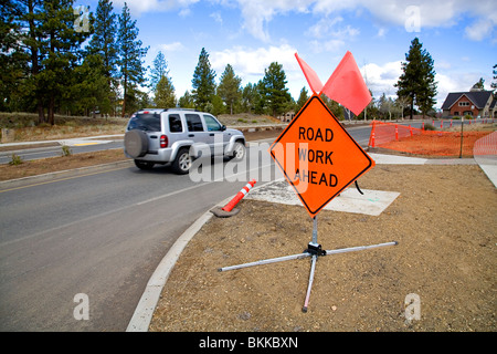 A Road Work Ahead sign warns motorists in a construction repair zone on a city street - Stock Photo