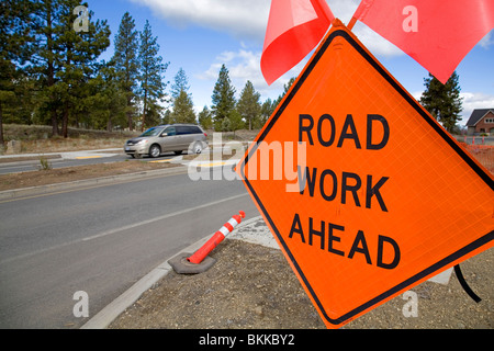 A Road Work Ahead sign warns motorists in a street construction repair zone on a city street - Stock Photo