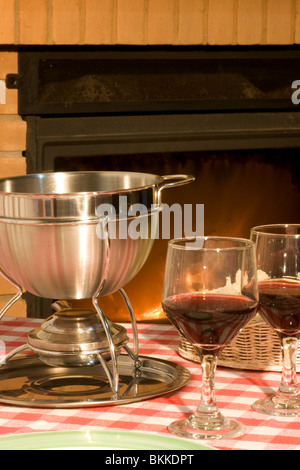 Cheese fondue and wine in front of a fireplace - Stock Photo