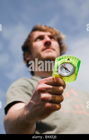 Young millennial man hiker using an orienteering compass in hand to point in right direction to go ahead looking - Stock Photo