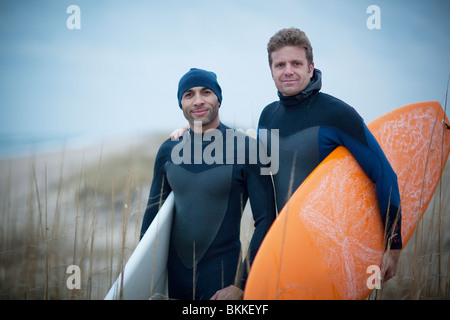 Men wearing wetsuits and carrying surfboards - Stock Photo