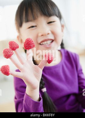 Chinese girl with raspberries on fingers - Stock Photo