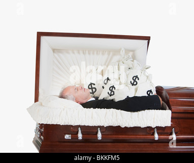 A Deceased Man In A Coffin Surrounded By Bags Of Money - Stock Photo
