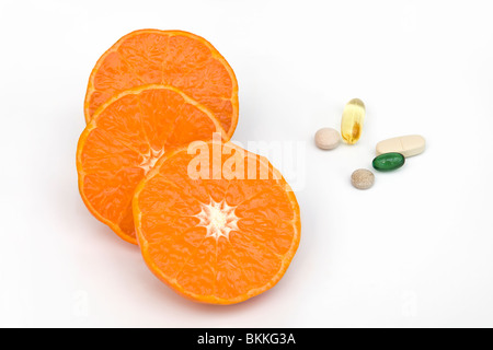 Clementine orange halves with a mixture of vitamin tablets which are multi vitamin, peppermint, gingko, ginseng - Stock Photo