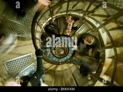 People climbing the 294 steps up the spiral staircase inside the Arc de Triomphe in Paris France - Stock Photo