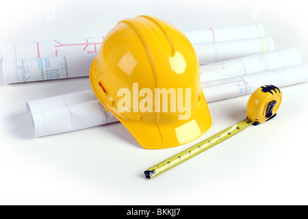 Architectural plans, hardhat and measuring tape over white table - Stock Photo