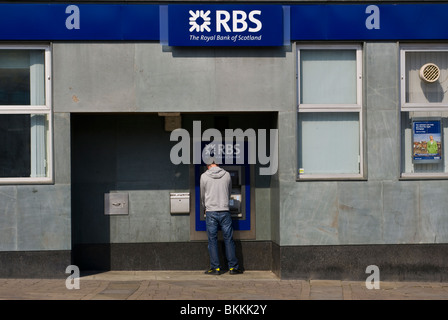 Man Using A Cash Machine At A Branch Of The Royal Bank Of Scotland - Stock Photo