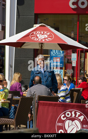 People Relaxing Together At Outside Tables Of A Costa Coffee - Stock Photo