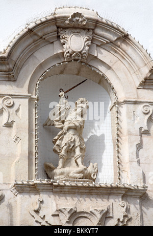 A statue of St Michael trampling on Satan within an alcove in the wall of the town hall in Alcaudete, Andalusia, - Stock Photo