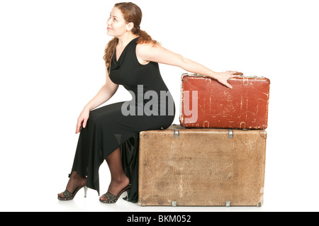 One beautiful woman in black dress dragging two ancient suitcases. Isolated on white background. - Stock Photo