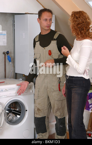 Handyman in coverall servicing domestic washing machine and explaining reparation to housewife giving professional - Stock Photo