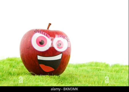 Funny apple with a face in the grass - Stock Photo
