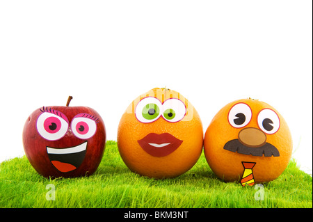 Funny healthy fruit family with faces in the grass - Stock Photo