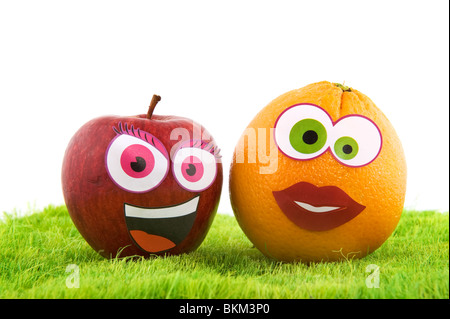 Funny healthy fruit with faces in the grass - Stock Photo
