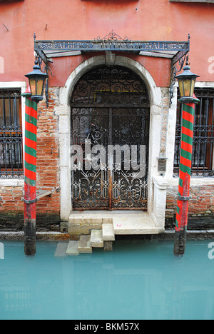 Colourful doorway and canal in Venice, Italy - Stock Photo