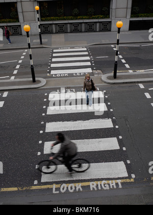 zebra pelican crossing, with cyclist crossing in front of pedestrian - Stock Photo